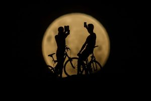 Cyclists take photos of the super moon in Lancelin, Australia Photograph: Paul Kane/Getty Images